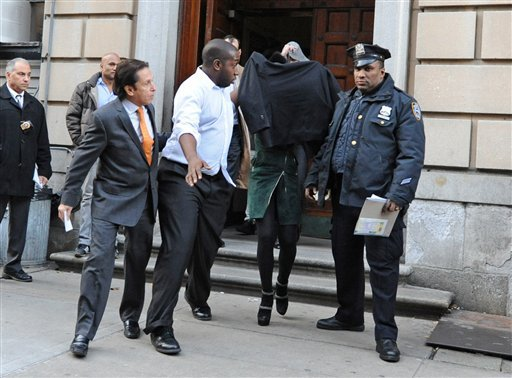 © Lindsay Lohan, second from right, is escorted from the 10th Precinct police station, with her face shielded, in this Nov. 29, 2012 file photo taken in New York after being charged for allegedly striking a woman at a nightclub.