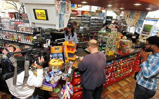 In this Nov. 29, 2012 file photo, members of the media document store cashier Tanice Stefanich helping a customer at a 4 Sons Food Store where one of the winning tickets in the $579.9 million Powerball jackpot was purchased in Fountain Hills, Ariz. (AP)