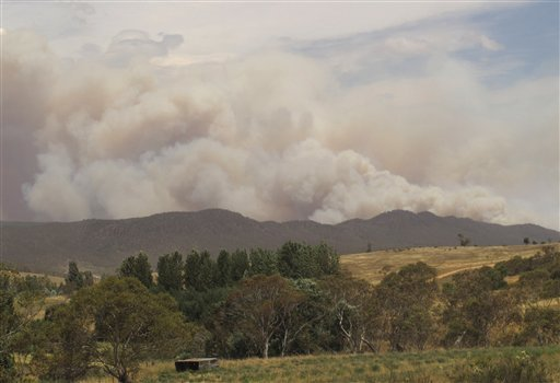 © Wildfire smoke rises from hills near the village of Numeralla in New South Wales state on Tuesday, Jan. 8, 2013. Wildfires raged across much of southeast Australia. (AP Photo/Rod McGuirk)