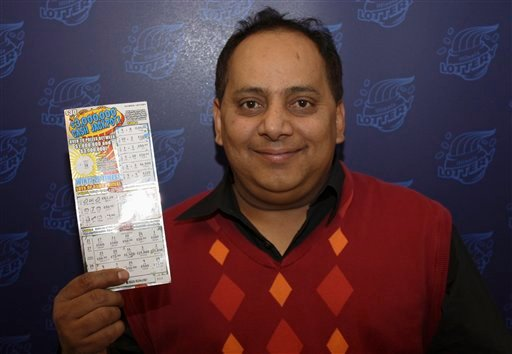 © This undated photo provided by the Illinois Lottery shows Urooj Khan, 46, of Chicago's West Rogers Park neighborhood, posing with a winning lottery ticket.