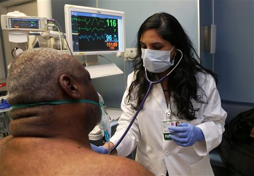 Dr. Meeta Khan wears a face mask as she examines a respiratory patient at the Rush University Hospital emergency department, Thursday, Jan. 10, 2013, in Chicago. (AP Photo/Charles Rex Arbogast)