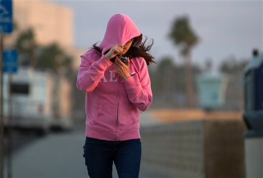 © Fiona Chiang shields her face from blowing sand as she walks north on Carlsbad Boulevard in Carlsbad, Calif. Thursday, Jan. 10, 2013. Southern California is bracing for a cold snap that is expected to drop temperatures to a six-year low.