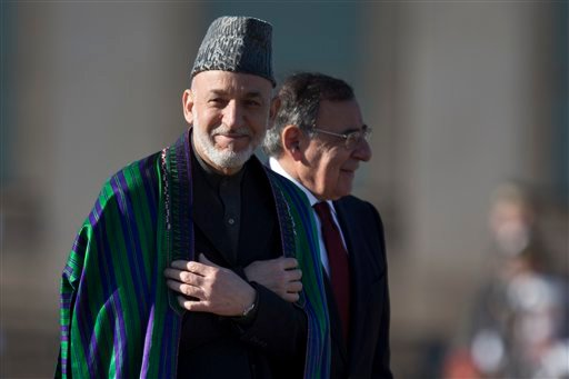 © Afghan President Hamid Karzai smiles as he and Defense Secretary Leon Panetta arrive for a full honors arrival ceremony, Thursday, Jan. 10, 2013, at the Pentagon. (AP Photo/ Evan Vucci)