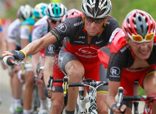 In this July 10, 2010, file photo, Lance Armstrong throws out his water bottle in the last kilometers of the climb toward Station les Rousses, France, during the seventh stage of the Tour de France. (AP Photo/Bas Czerwinski, File)