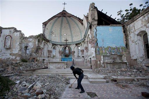 © A man sweeps an exposed tiled area of the earthquake-damaged Santa Ana Catholic church, where he now lives, in Port-au-Prince, Haiti, Saturday, Jan. 12, 2013.