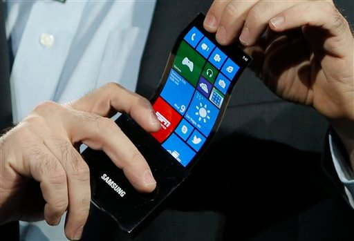 © Eric Rudder, chief technical strategy officer of Microsoft, holds a prototype Windows smartphone with a flexible OLED display during Samsung's keynote address at the International Consumer Electronics Show in Las Vegas, Wednesday, Jan. 9, 2013.