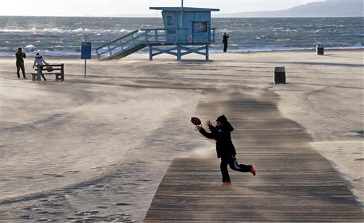 Bundled up against the elements, a boy catches a football as frigid, gusting winds blow sand in drifts across a boardwalk on a nearly-deserted beach near the pier at Santa Monica, Calif., Thursday, Jan. 10, 2013. (AP)