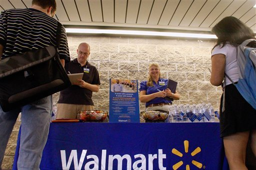 In this Thursday, Sept. 1, 2011, photo, Wal-Mart employees Jon Christians and Lori Harris take job applications and answers questions during a job fair at the University of Illinois Springfield campus in Springfield, Ill. (AP Photo/Seth Perlman)