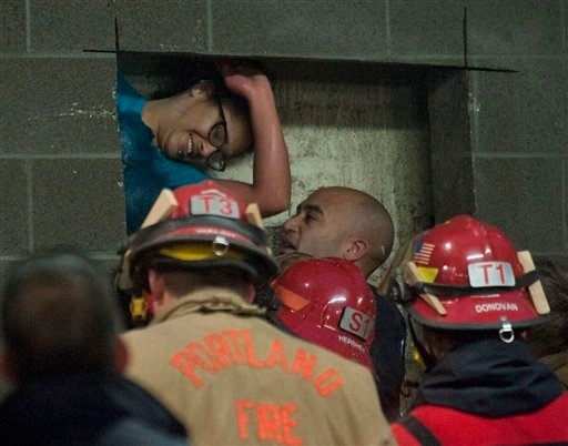 A woman is rescued from being trapped inside a wall of the parking garage at the Gretchen Kafoury Commons in SW Portland, Ore., Wednesday, Jan. 16, 2013. Portland firefighters worked for over three and a half hours cutting her free. (AP Photo)