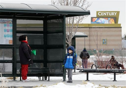 A woman and her grandson wait for a bus, near the fenced-in Century movie theater, the site of the deadly 2011 shootings, in Aurora, Colorado, Tuesday, Jan. 15, 2013. (AP Photo/Brennan Linsley)