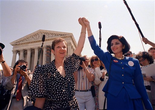 © In this Wednesday, April 26, 1989 file photo, Norma McCorvey, Jane Roe in the 1973 court case, left, and her attorney Gloria Allred hold hands as they leave the Supreme Court building in Washington.