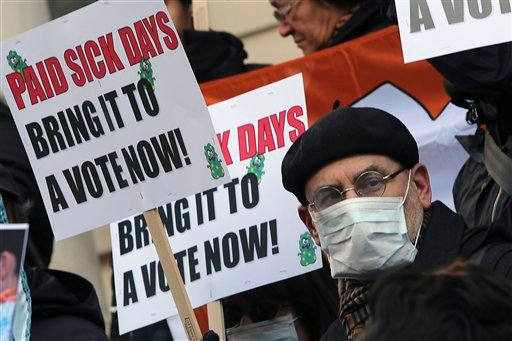  In this Friday, Jan. 18 2013 photo, activists hold signs during a rally at New York's City Hall to call for immediate action on paid sick days legislation in light of the continued spread of the flu.