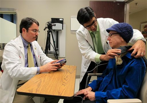 © Dr. Doug Scharre, left, and Dr. Punit Agrawal, center, prepare Kathleen Sanford's deep brain stimulation device for monitoring Monday, Dec. 17, 2012, in Columbus, Ohio.