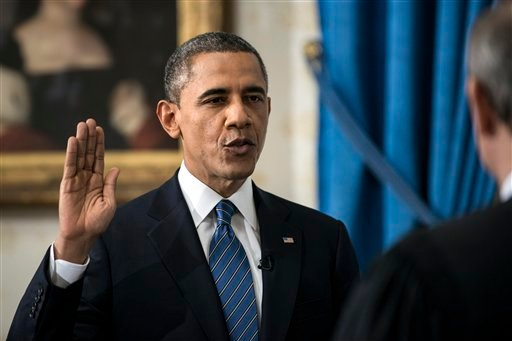 © President Barack Obama is officially sworn-in by Chief Justice John Roberts, not pictured, in the Blue Room of the White House Sunday, Jan. 20, 2013, in Washington.