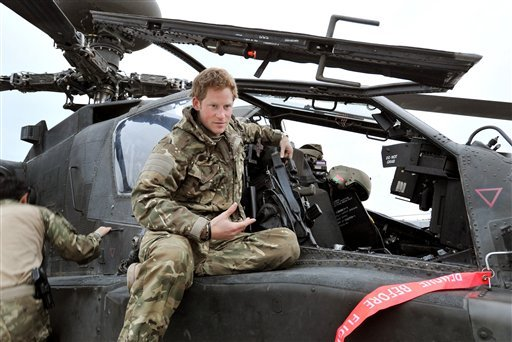 In this photo taken Dec. 12, 2012, made available Monday Jan. 21, 2013 of Britain's Prince Harry or just plain Captain Wales as he is known in the British Army, talks to a TV crew after making his early morning pre-flight checks on the flight-line. (AP)