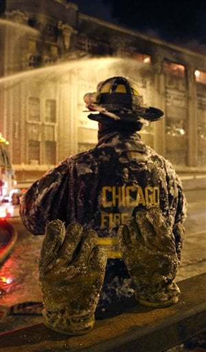 The frozen ice covered pair of gloves belonging to a Chicago firefighter stand on a railing behind him in single digit temperatures Wednesday, Jan. 23, 2013, in Chicago. (AP Photo/Charles Rex Arbogast)