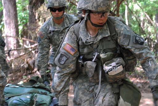 In a May 9, 2012 file photo, Capt. Sara Rodriguez, 26, of the 101st Airborne Division, carries a litter of sandbags during the Expert Field Medical Badge training at Fort Campbell, Ky.
