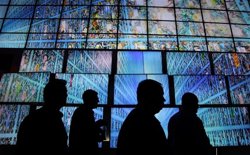 © In this Thursday, Jan. 6, 2011, file photo, exhibitors and buyers at the Consumer Electronics Show walk by a display of LG HDTV screens, in Las Vegas.
