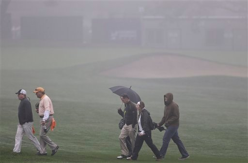 © Golf fans cross a fairway in the fog at Torrey Pines golf course during a weather delay before the start of the third round of the Farmers Insurance Open golf tournament Saturday, Jan. 26, 2013, in San Diego. (AP Photo/Lenny Ignelzi)