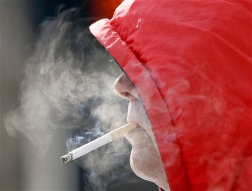 ©  In this Wednesday, Feb. 14, 2007 file photo, a man smokes in Omaha, Neb. Annual health care costs are roughly $96 billion for smokers and $147 billion for the obese, the government says.