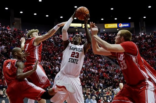 © San Diego State's Deshawn Stephens, center, grabs an offensive rebound surrounded by New Mexico's Chad Adams (4), Hugh Greenwood (3) and Alex Kirk, right, in the second half during an NCAA college basketball game Saturday, Jan. 26, 2013, in San Diego.