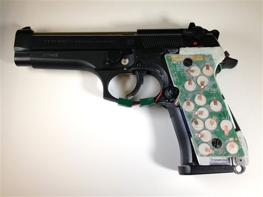 © This photo provided by the New Jersey Institute of Technology shows a 9-mm semi-automatic handgun configured with transducers to its handle that can detect the grasp of an authorized user.