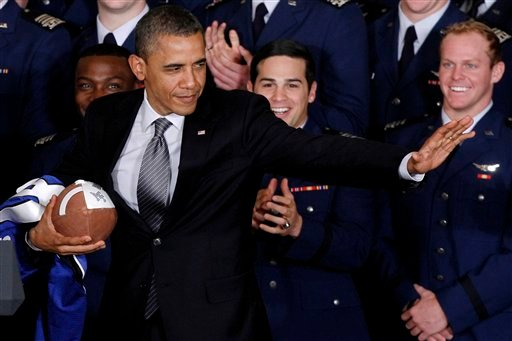 ©  In this April 23, 2012 file photo, President Obama strikes the Heisman pose after he awarded the Commander-in-Chief Trophy to the Air Force Academy football team at the White House in Washington.
