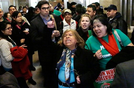©  In this Jan. 7, 2013 file photo, supporters of granting illegal immigrants drivers licenses cheer after a House committee hearing at the Illinois State Capitol in Springfield.