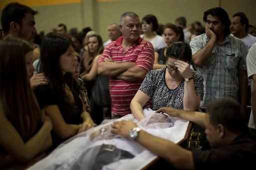 © Relatives and friends mourn on the coffin containing the remains of a fire victim at a gymnasium where bodies were brought for identification in Santa Maria city, Rio Grande do Sul state, Brazil, Sunday, Jan. 27, 2013.