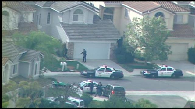Law enforcement officers search the neighborhood of Tierrasanta for a homicide suspect Tuesday, January 29, 2013.