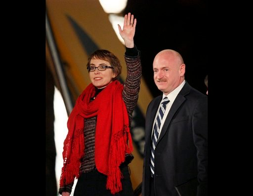 Rep. Gabrielle Giffords and her husband Mark Kelly, wave at the start of a memorial vigil in this Jan. 8, 2012 file photo taken in Tucson, Ariz. (AP Photo/Matt York, File)