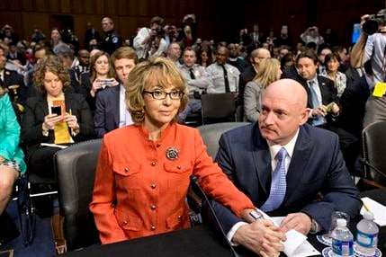 Fmr Arizona Rep. Gabrielle Giffords sits with her husband, Mark Kelly, on Capitol Hill in Washington, Jan. 30, 2013, prior to speaking before the Senate Judiciary Committee. (AP Photo/J. Scott Applewhite)