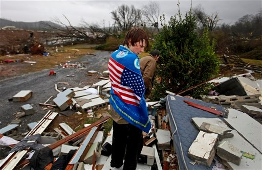Will Carter wraps himself up in a towel he found while searching debris for the family dog, upon arriving to his damaged home from school following a tornado Jan. 30, 2013, in Adairsville, Ga. (AP Photo/David Goldman)