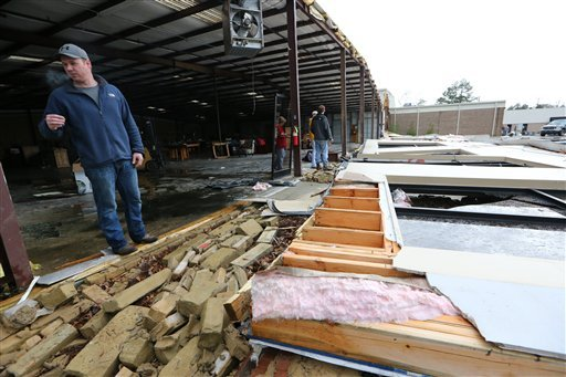 Marshall Faulkner surveys damage to his family's business in Tupelo, Mississippi on Wednesday, January 30, 2013. (AP Photo/The Northeast Mississippi Daily Journal, C. Todd Sherman)