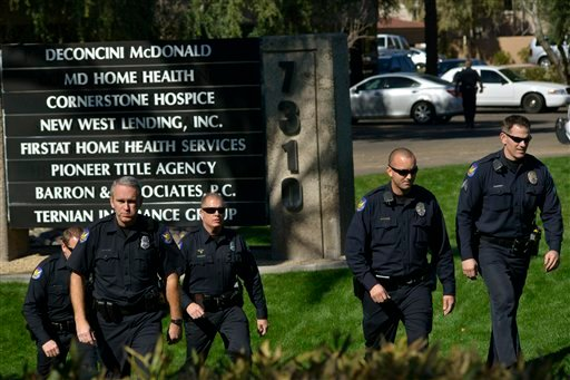 Police officers leave an office building after a shooting at the building in Phoenix on Wednesday, Jan. 30, 2013. (AP Photo/Patrick Sison)