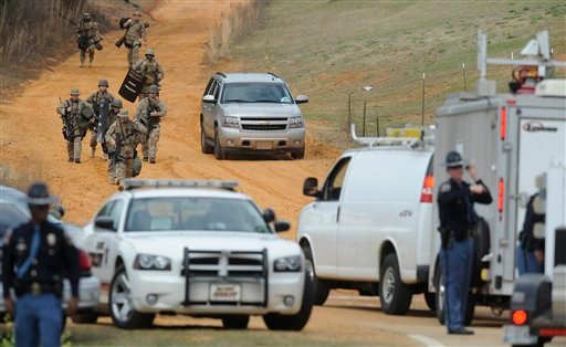 Heavily armed men move away from the suspects home at the scene of a Dale County hostage scene in Midland City, Ala. on Wednesday Jan. 30, 2013. (AP Photo/Montgomery Advertiser, Mickey Welsh)