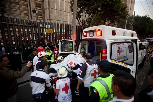 © An injured person is carried into an ambulance after an explosion at an adjacent building to the executive tower of Mexico's state-owned oil company PEMEX, in Mexico City, Thursday Jan. 31, 2013.
