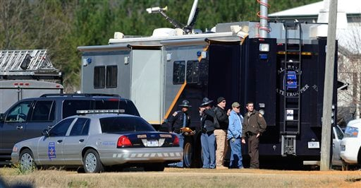 © Law officers stand beside the Alabama State trooper mobile command post at the Dale County hostage scene in Midland City, Ala. on Thursday, Jan. 31, 2013.