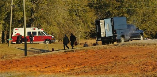 Police and emergency personnel remain on site at the property of Jimmy Lee Sykes, a suspect accused of holding a 5-year-old boy hostage in an underground bunker on Saturday Feb. 2, 2013 in Midland City, Ala. (AP Photo/al.com, Joe Songer)