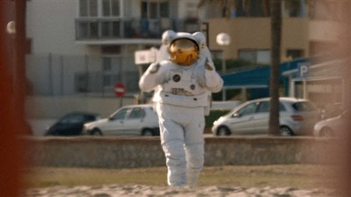 © This undated screenshot provided by Axe shows the Super Bowl advertisement for Axe. Axe's 30-second ad in the third quarter of the game shows a woman in the ocean getting rescued by a sexy lifeguard, but going for an astronaut instead.