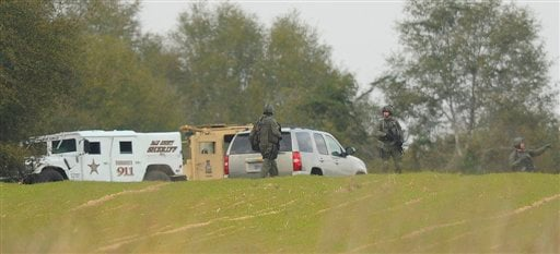 Armed law enforcement personnel station themselves near the property of Jimmy Lee Sykes, Monday, Feb. 4, 2013 in Midland City, Ala. (AP Photo/AL.com, Joe Songer)