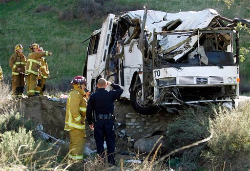 © Firefighters and a California Highway Patrol officer survey the scene of an accident where at least eight people were killed and 38 people were injured after a tour bus, left, carrying a group from Tijuana, Mexico crashed with two other vehicles.