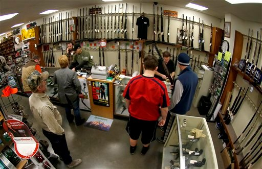 © In this Jan. 16, 2013 file photo, taken with a fisheye lens, customers line up at the gun counter at Duke's Sport Shop in New Castle, Pa.