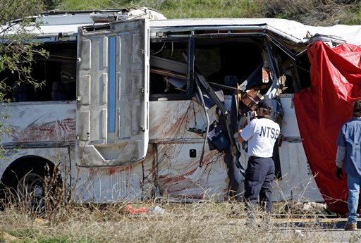 Bolldstains and personal items are seen as an investigator from the National Transpoartation Safety Board photographs a tour bus after an accident that killed at least eight people.