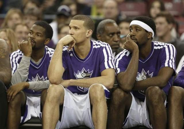 Sacramento Kings' Aaron Brooks, left, Francisco Garcia, center, and John Salmons watch the closing moments of an NBA basketball game against the Memphis Grizzlies in Sacramento, Calif.