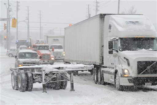 © A truck tries to get past a trailer that was left by the side of the road during a snowstorm in Toronto on Friday, Feb. 8, 2013.