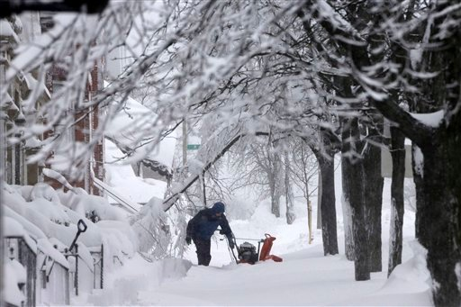 © A man clears snow from the front of his home on Third Street in the South Boston neighborhood of Boston on Saturday, Feb. 9, 2013. (AP Photo/Gene J. Puskar)