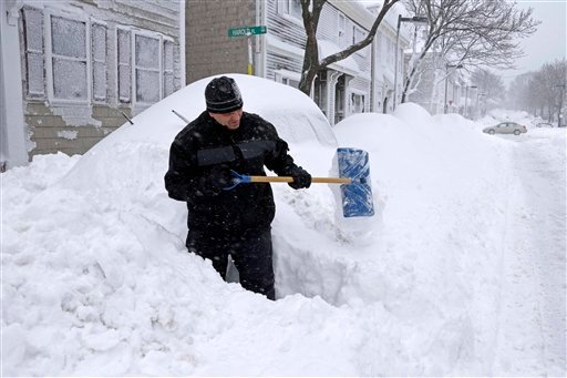 © John Silver shovels between buried cars in front of his home on Third street in the South Boston neighborhood of Boston, Saturday, Feb. 9, 2013.