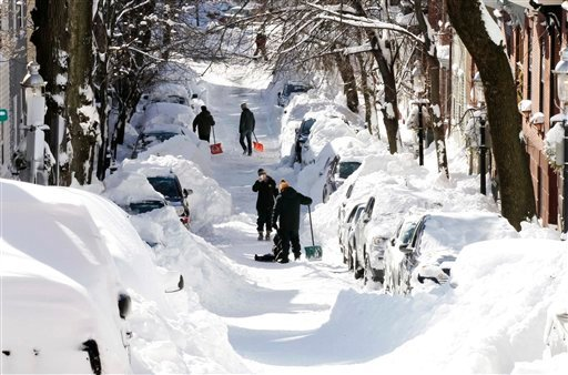  People pause for a picture while digging out their cars in Boston, Sunday, Feb. 10, 2013.