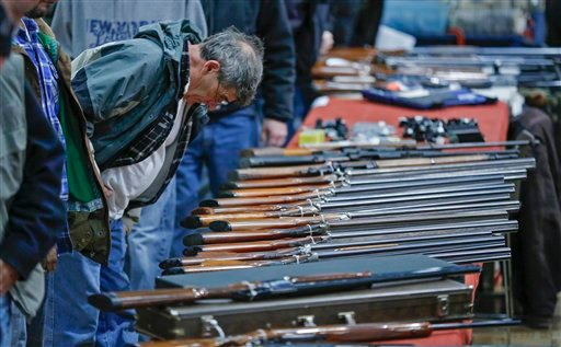 © In this Jan. 26, 2013 file photo, a customer looks over shotguns on display at the annual New York State Arms Collectors Association Albany Gun Show at the Empire State Plaza Convention Center in Albany, N.Y.